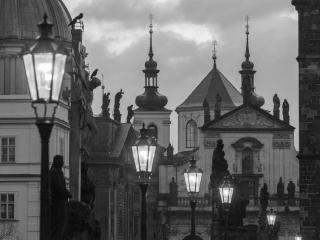 Lampy Karlova mostu v pozadí střechy Starého města